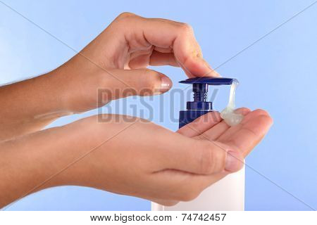 Female hands using liquid soap on light blue background