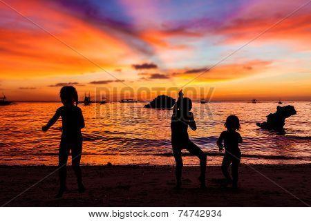 three kid silhouettes on sunset sea background