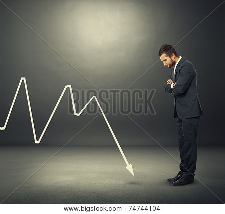 despondent businessman looking at negative graph over dark background