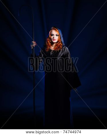 Young witch on blue rays background