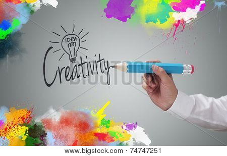 Businessman writing the word creativity and painting abstract colorful design on gray background concept for business idea, imagination and inspiration
