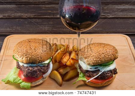 hamburger and french fries on a wooden plate.