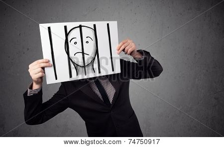 Businessman holding a paper with a prisoner in jail behind the bars on it in front of his head