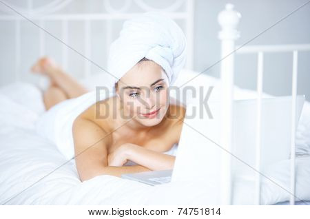 Gorgeous young woman relaxing with her hair in a clean fresh white towel lying on her bed reading a laptop computer with a smile on her face