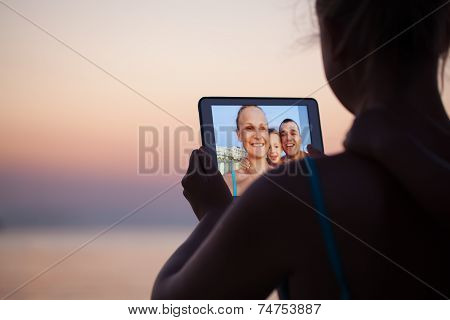 Family selfie with pad on the beach