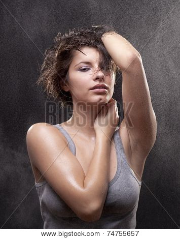 Wet young woman with a torn shirt  Fine spray of water. Post production - without styling filters