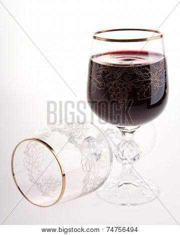 Red wine into wine glass and empty fallen glass