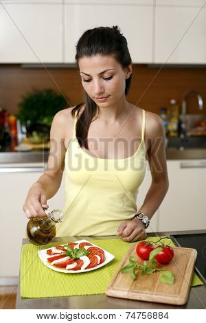 Young beautiful woman making salad with tomatoes, cheese, basil and oil  in the kitchen