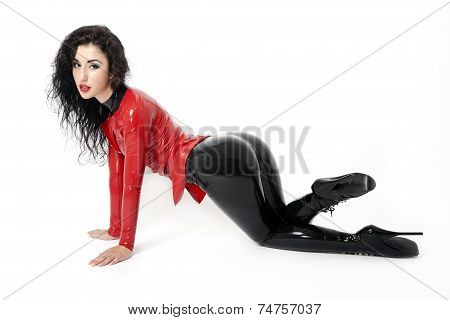 Sexy flexible brunette in black and red latex and boots whit high heels kneeling