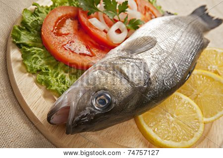 Freshly Bass Fish with vegetables on wooden cutting board