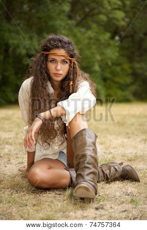 Beautiful hippie girl with rope in the park. Romantic. White shirt, short jeans and leather boots
