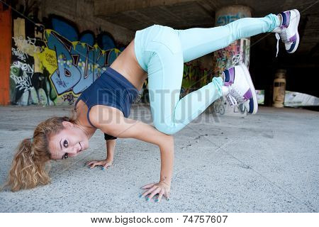 Happy active hip teenage blonde girl breakdancing  outdoors on street near wall with graffiti