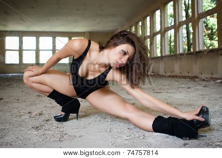 Brunette woman in black leotard and high heels, dancing in old building