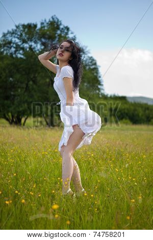 Sexy lovely young woman posing on grass field