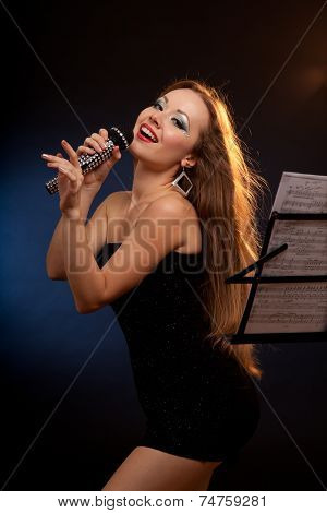 Portrait of a young woman in black dress singing