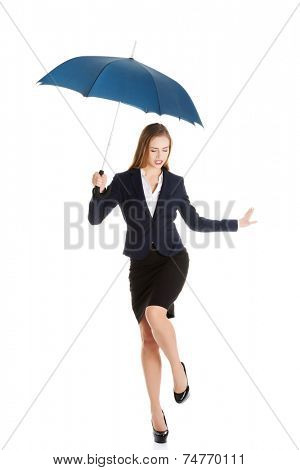 Blonde businesswoman dancing with umbrella
