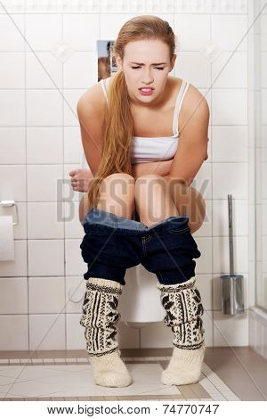 Young woman sitting on a toilet