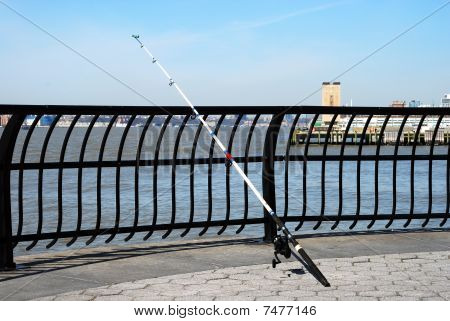 A fishing rod leaned on the fence under a blue sky
