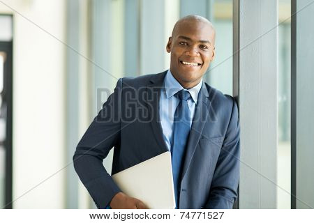 handsome afro american businessman holding laptop computer