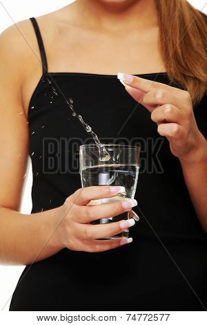 Tanned woman holding a glass of aspirin