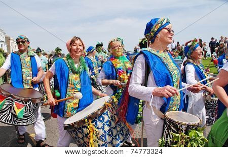 HASTINGS, ENGLAND - MAY 5, 2014: The Dende Nation samba drum troupe perform at the parade on the West Hill during the annual Jack In The Green festival. The event marks the May Day public holiday.