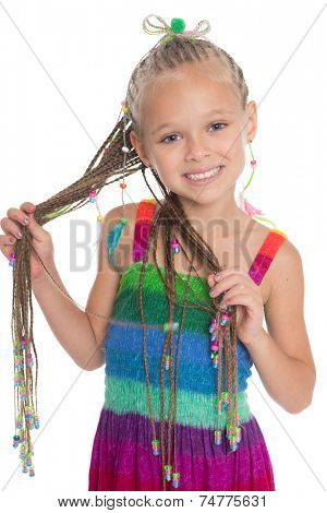 Cute little girl with dreadlocks in her hands. The girl is six years old.