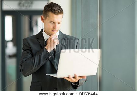 handsome businessman reading email on his laptop