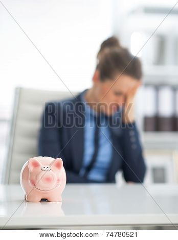 Closeup On Piggy Bank And Frustrated Business Woman In Backgroun