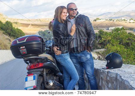 Happy couple traveling by motorbike