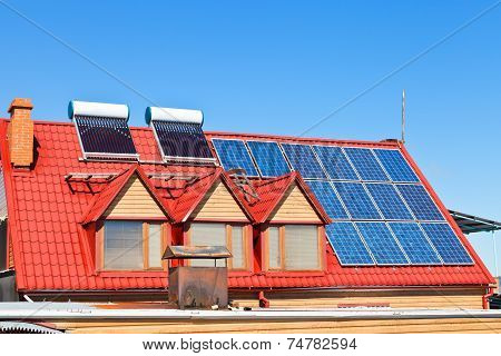 Solar Batteries And Heaters On Home Roof