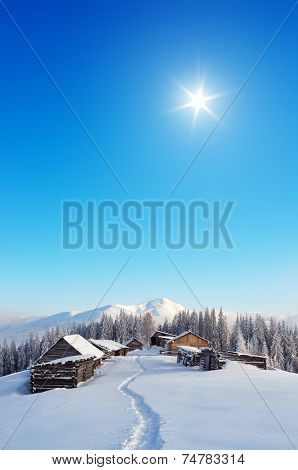 Snowy trail to the mountain village. Winter landscape with huts in the mountains. Carpathians, Ukraine, Europe