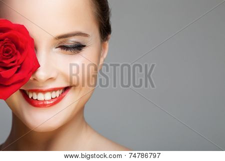 Close-up portrait of beautiful smiling woman with red rose. Make-up face.