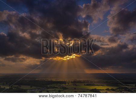 Crepuscular Rays Of Sunlight Shine Onto Fields In Dorset