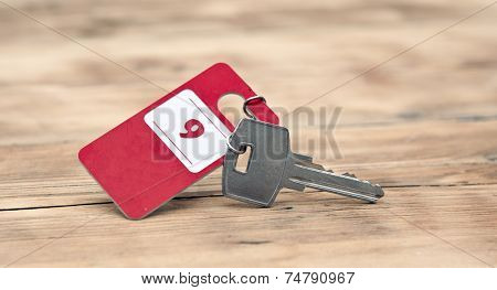 Hotel suite key with room number 9 on wood table
