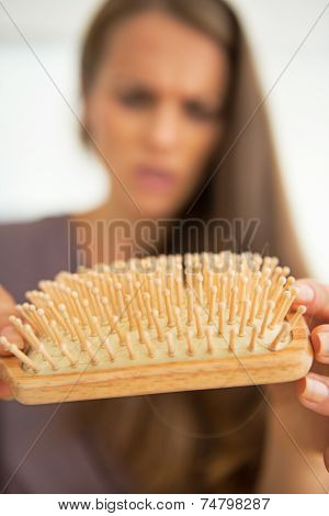 Closeup On Concerned Woman Looking On Hair Comb