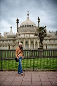Young woman posing in front of the Brighton Palace Pavilion , a British Royal pleasure palace built in Indo-Saracenic style with ornate onion domes, columns and arches, a popular tourist destination poster