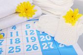 pic of menses  - Sanitary pads and yellow flowers on blue calendar background - JPG