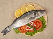 image of bass fish  - Freshly Bass Fish with vegetables on wooden cutting board - JPG