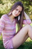 stock photo of tunic  - Pretty woman with pink tunic in the park sitting on grass - JPG