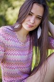 foto of tunic  - Pretty woman with pink tunic in the park sitting on grass - JPG