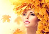 Photo of autumn woman with yellow leaves hair style. Autumn lady portrait. Beauty fashion model girl with autumnal make up and hairstyle. Fall. Creative autumn makeup. Beautiful face.