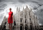 pic of milan  - Portrait of a beautiful woman in red carrying some shopping bags standing in front of the Cathedral of Milan - JPG