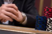 foto of shiting  - red blue and shite chips in piles near player sitting at table  in casino with selective focus - JPG