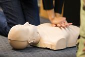 picture of paramedic  - A group of adult education students practitcing CPR chest compressioon on a dummy - JPG