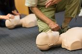 foto of cpr  - Seniror first aid student practitcing CPR on a dummy - JPG