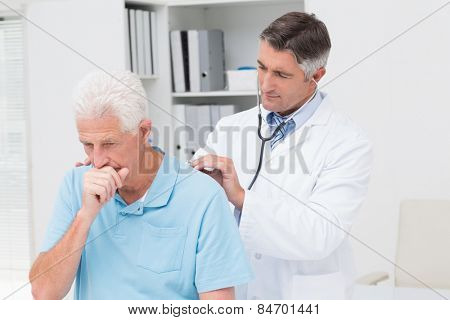 Male doctor examining coughing senior patient in clinic