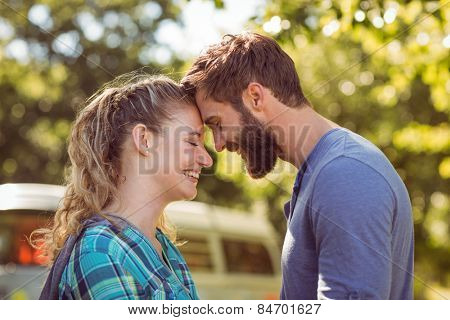 Hipster couple smiling at each other on a summers day