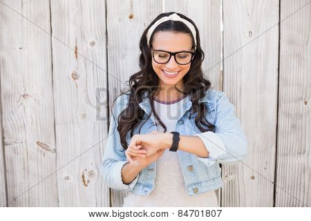 Pretty hipster checking the time against bleached wooden fence