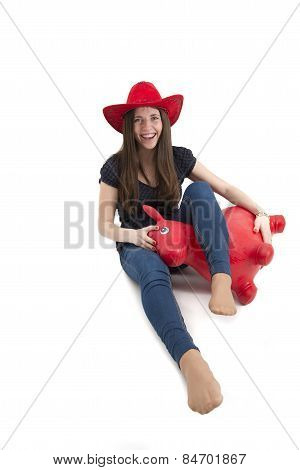 Young Girl With Red Cowboy Hat Riding O Toy Horse Isolated