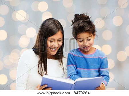 family, children, education and happy people concept - happy mother and little daughter reading book over holidays lights background